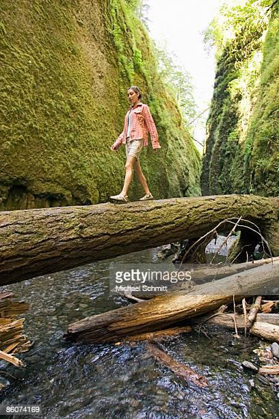 Hiker walking across fallen log