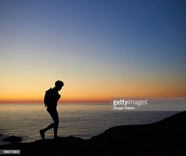 Hiker walking along coastline at sunset.