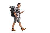 Full length profile shot of a hiker walking and looking at a mobile phone isolated on white background