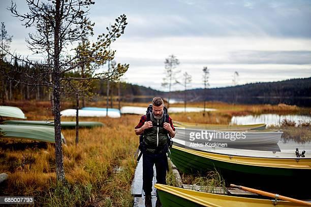 Hiker walking by lake with boats, Kesankijarvi, Lapland, Finland