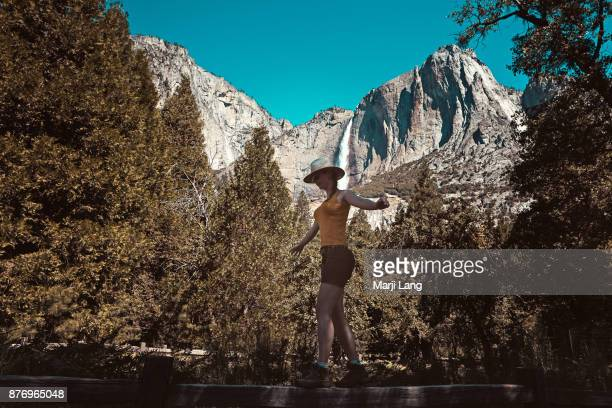 Hiker walking by the Bridalveil falls in the background Yosemite National Park California USA