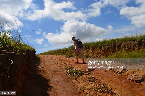 Hiker Walking On Footpath On Mountain Against Cloudy Sky