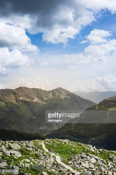 Hiker walking on high mountain trail