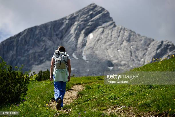 A hiker walks along a path in the Bavarian Alps on June 26 2015 near GarmischPartenkirchen Germany The Bavarian Alps are a popular summer tourist...