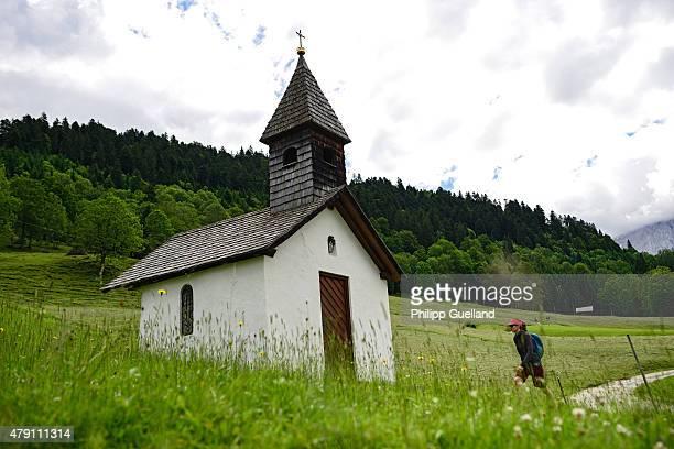 A hiker walks towards a small chapel in the Bavarian Alps on June 24 2015 near GarmischPartenkirchen Germany The Bavarian Alps are a popular summer...