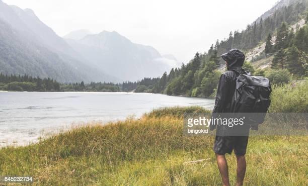 Wanderer mit einem Rucksack beobachten den See umgeben von Bergen