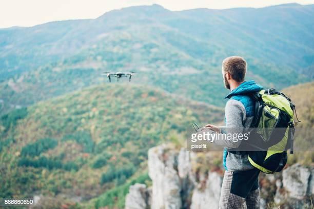 Randonneur avec un drone haut dans la montagne