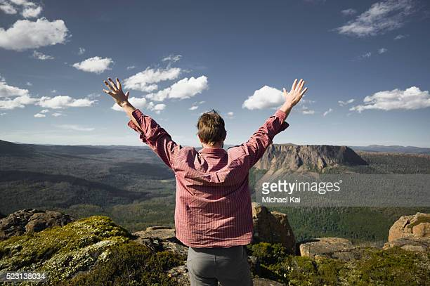Hiker with arms spread looking at mountain landscape, Falling Mountain, Tasmania, Australia