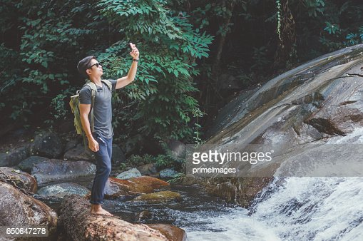 Hiker with backpack and laptop and phone at  waterfall  the forest. : Bildbanksbilder