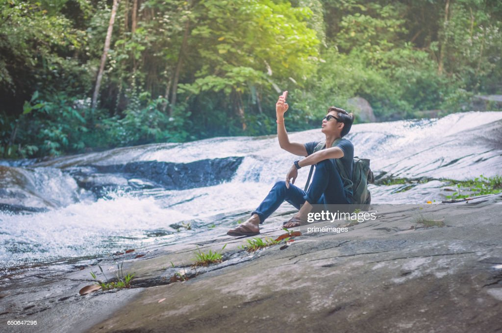 Hiker with backpack and laptop and phone at  waterfall  the forest. : Foto stock