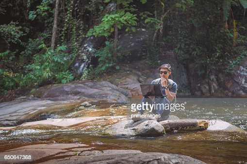 Hiker with backpack and laptop and phone at  waterfall  the forest. : Photo