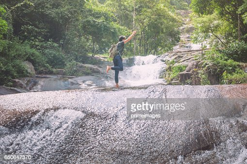 Hiker with backpack and laptop and phone at  waterfall  the forest. : Stock Photo