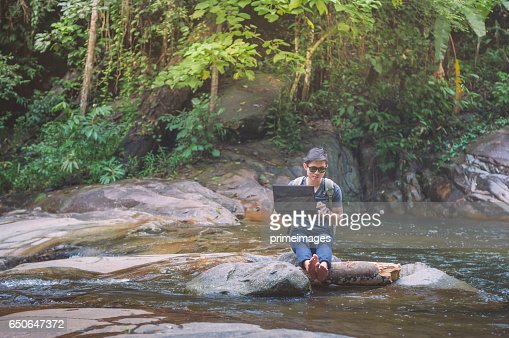 Hiker with backpack and laptop and phone at  waterfall  the forest. : Stockfoto