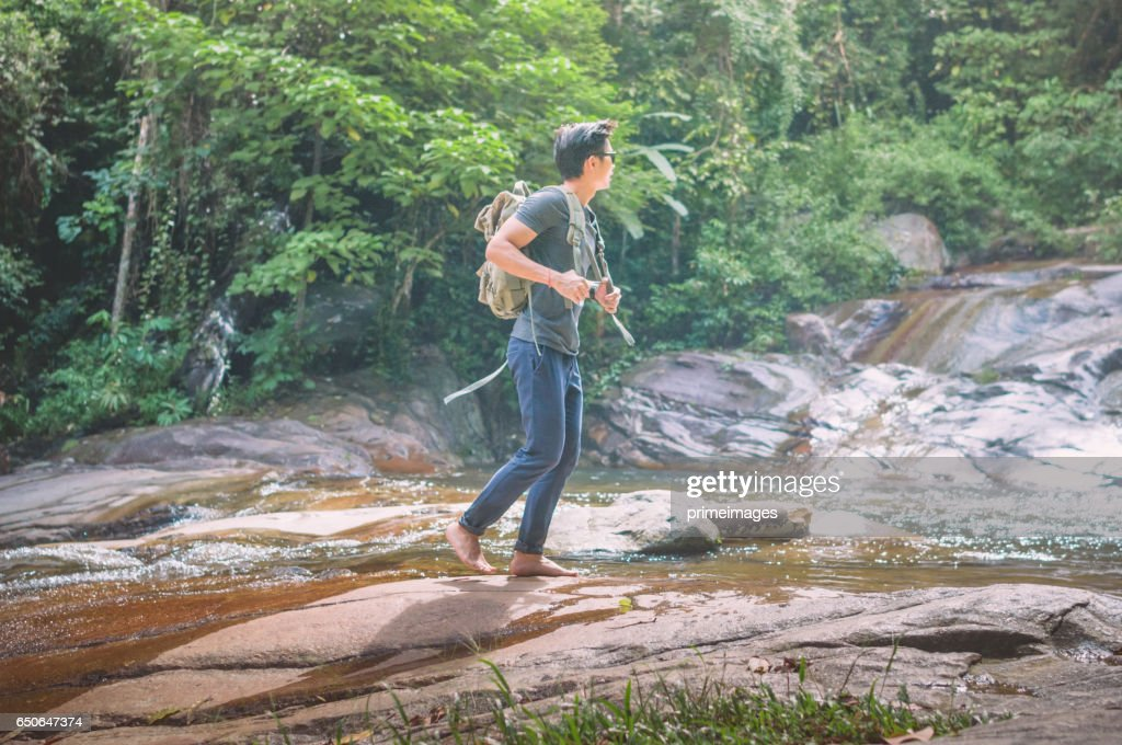Hiker with backpack and laptop and phone at  waterfall  the forest. : ストックフォト
