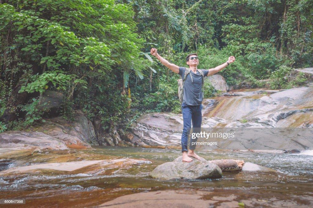Wandelaar met rugzak en laptop en telefoon bij waterval het bos. : Stockfoto