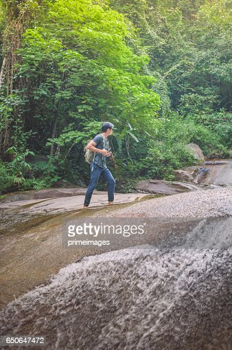 Hiker with backpack and laptop and phone at  waterfall  the forest. : Stock-Foto