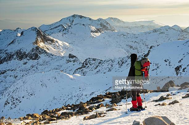 Hiker with backpack and snowshoes in mountain