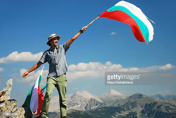 Hiker with Bulgarian flag at mountain summit
