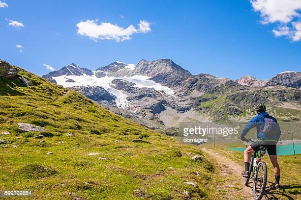 Hiker with mountain bike near alpine lake