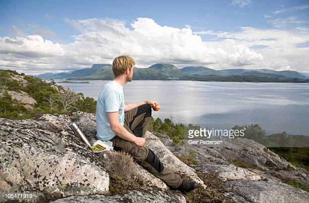 Hiker with packed lunch on rock above fjord
