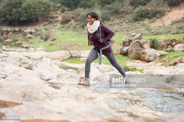 Hiker woman outdoors walking crossing river creek.