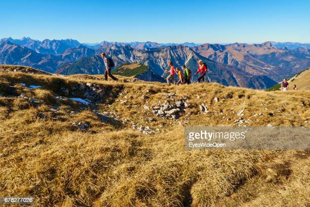 Hikers are climbing in the Alps with a Panoramic View of the Mountains of Rofan on November 01 2015 in Achensee Tyrol Austria