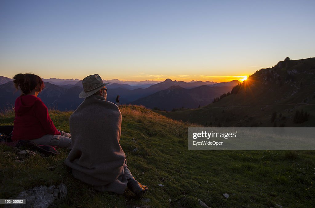 Hikers are watching the sunset at the mountain of Rotwand with a panoramic view of the so called Blue Bavarian Alps on August 29, 2012 in Spitzingsee, Bavaria, Germany.