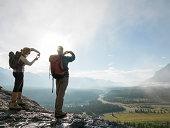 Hikers compose pictures on ledge above fog, mtns