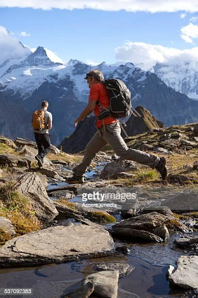 Hikers cross stream, walk through meadow