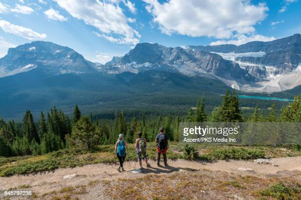Hikers follow mountain trail above distant valley