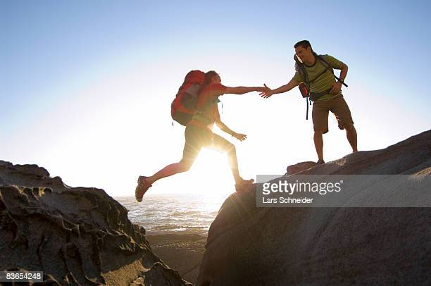 Hikers jump on rocky Pacific coast.