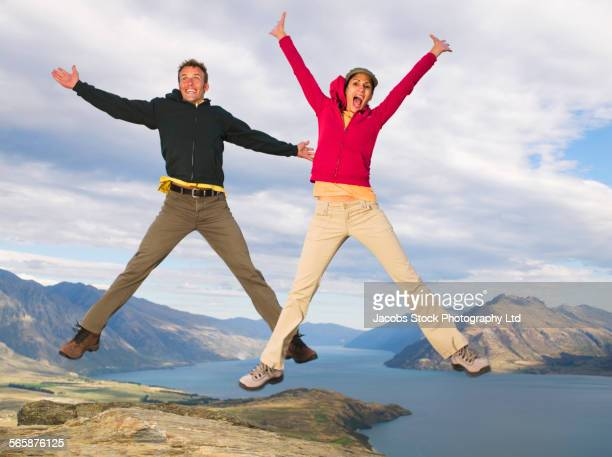 Hikers jumping for joy on remote hilltop, Queenstown, South Island, New Zealand