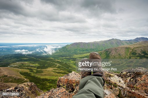 POV of hikers legs and feet as he rests and enjoys the view from Flat Top Mountain overlooking the Anchorage bowl, Southcentral Alaska, Summer