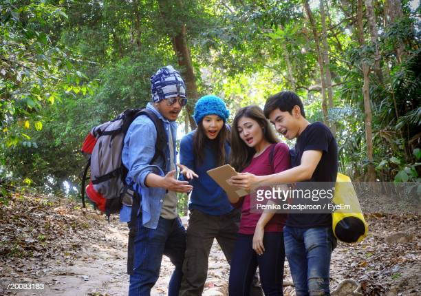 Hikers Looking Into Digital Tablet At Forest