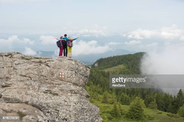 Hikers on top of high cliff in the mountains