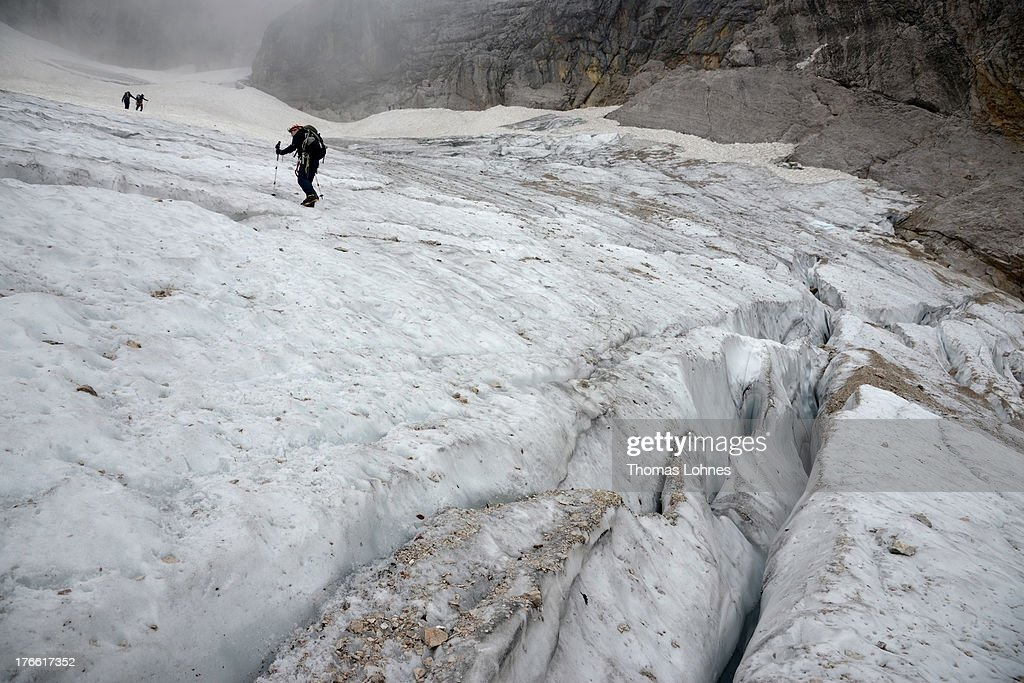 Hikers pass the glacier on the way to Germany's highest mountain Zugspitze (2.962 meter) in the Alps near the village of Garmisch-Partenkirchen on August 14, 2013 in Garmisch-Partenkirchen, Germany.