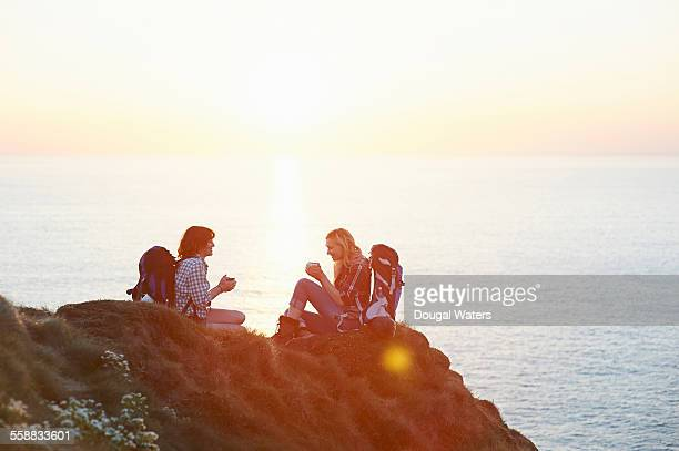 Hikers rest with hot drink at sunset