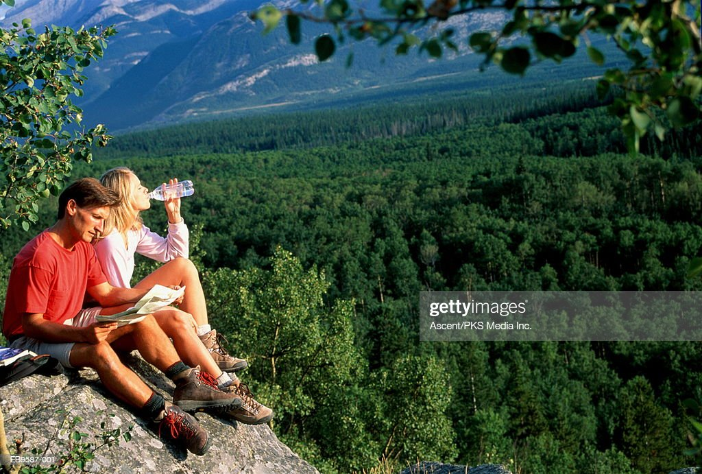Hikers resting on rocks above valley, checking map and drinking : Stock Photo