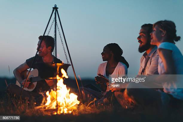 Hikers Singing And Playing Guitar Around Campfire