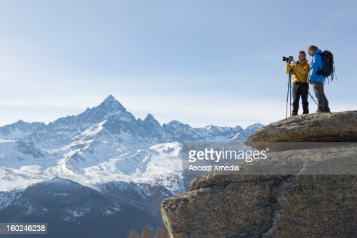 Hikers stand on mountain summit, taking picture : Stock Photo