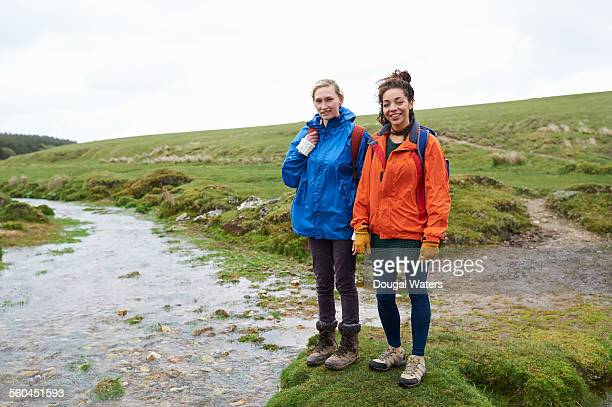 Hikers standing by stream in countryside