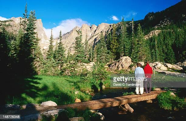 Hikers standing on log bridge below Dream Lake, with Hallett Peak beyond trees.