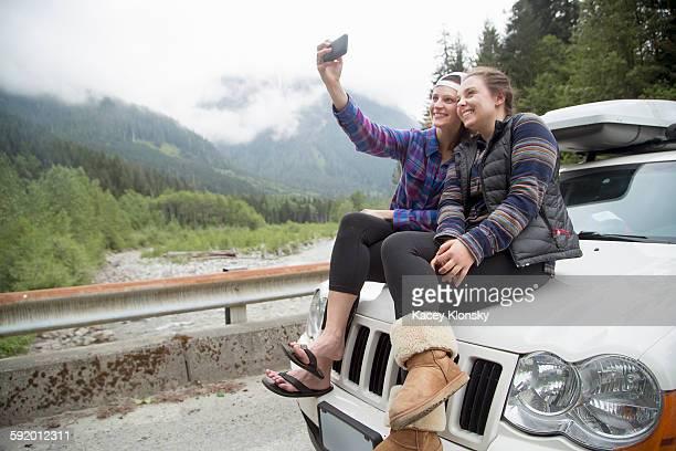 Hikers taking selfie with smartphone on bonnet of vehicle, Lake Blanco, Washington, USA