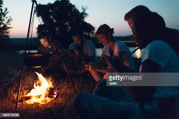 Hikers Using Smart Phones Around Campfire.