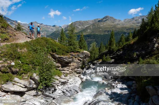 Hikers walk beside a stream, Parco Naturale Vedrette di Ries - Aurina, South Tyrol