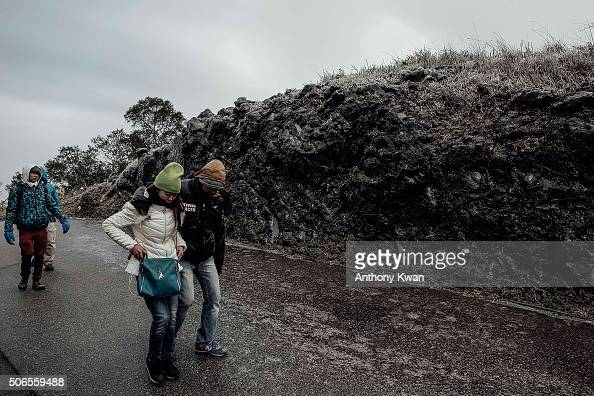 Hikers walk on icy road in subzero temperature at Kowloon Peak on January 24 2016 in Hong Kong Hong Kong Hong Kong was hit by a cold snap today with...