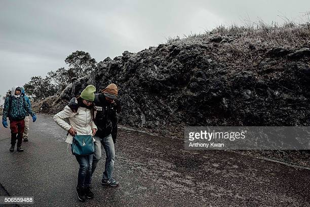 Hikers walk on icy road in subzero temperature at Kowloon Peak on January 24 2016 in Hong Kong Hong Kong Hong Kong was hit by a cold snap today with...