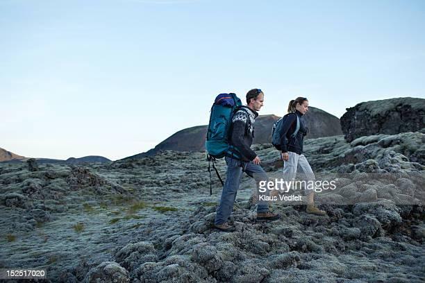 2 hikers walking in lava landscape