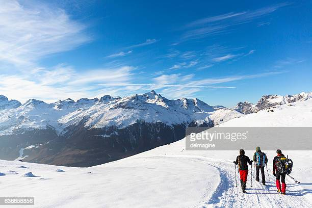Hikers walking on snow covered road in high mountain