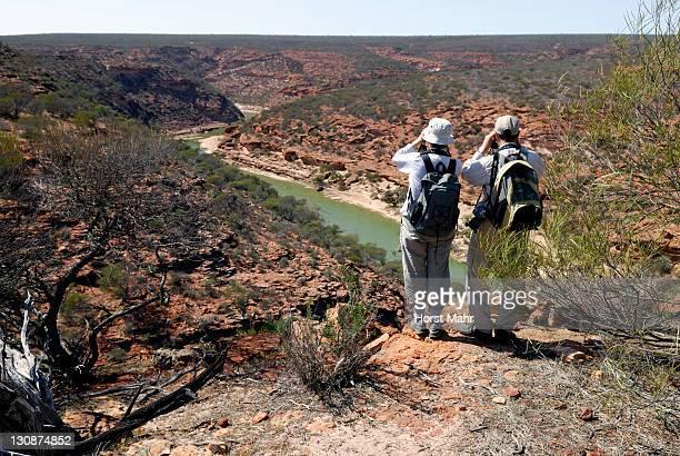 Hikers with field glasses overlooking the Murchison River, Kalbarri National Park, Western Australia, Australia
